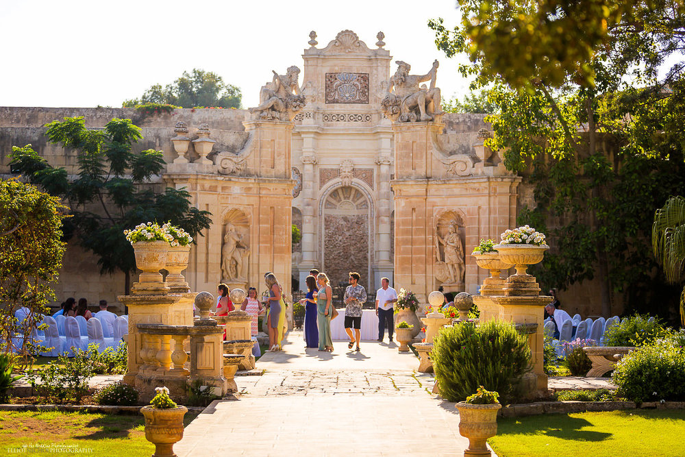 Wedding guest make their way to the wedding ceremony in the Baroque gardens at Villa Bologna, Malta.