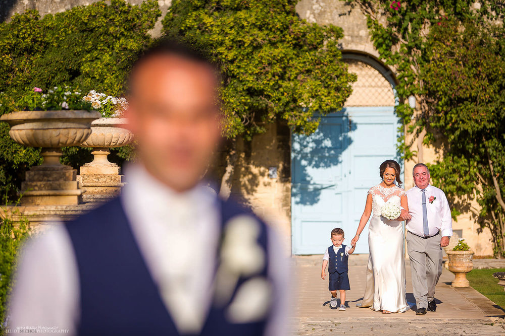 Bride and her father make their way to the civil ceremony at Villa Bologna, Malta.