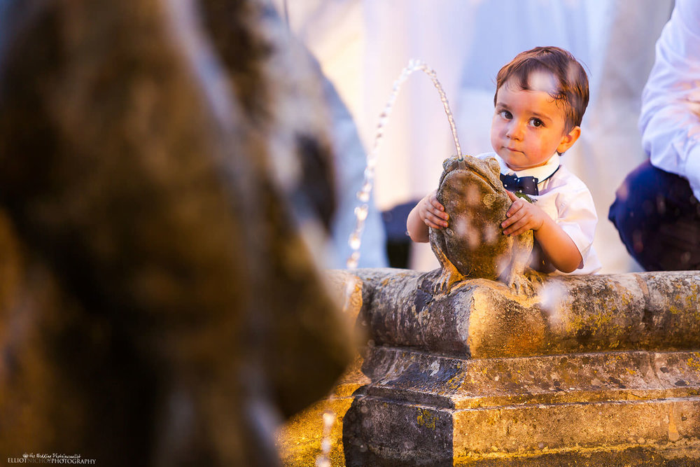 young guest plays with a water feature in the gardens of Villa Bologna, Malta.