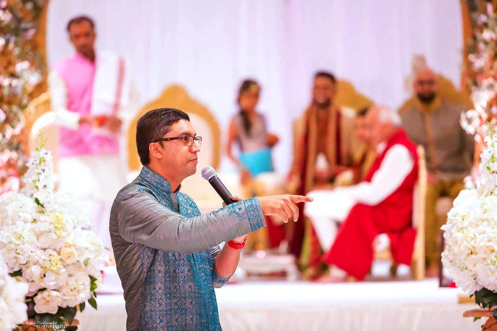 Speaker during the Indian Hindu wedding ceremony at Chateau Impney, UK. Photo by Newcastle Upon Tyne based wedding photojournalist Elliot Nichol.