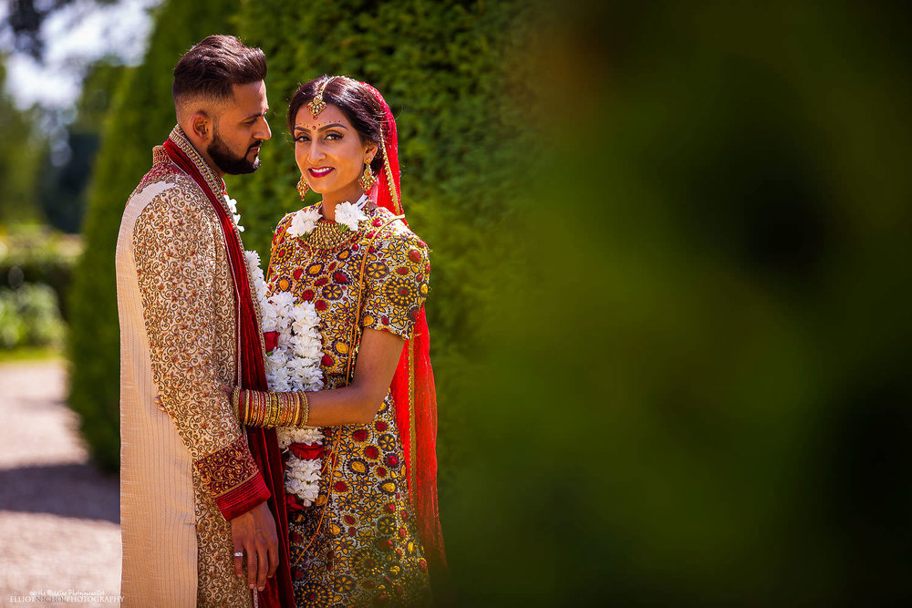 Portrait of the Bride & Groom in their Indian Hindu wedding dress in the grounds of Chateau Impney. Photo by Newcastle Upon Tyne based wedding photojournalist Elliot Nichol.
