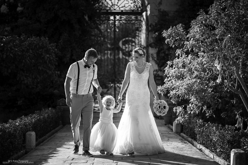 Young family on their wedding day walking through the gardens of the wedding venue Palazzo Parisio in Malta.