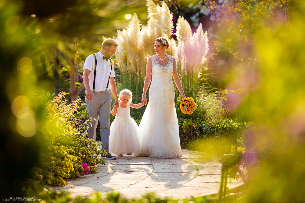 Newlyweds walk through the gardens of the Maltese wedding venue Palazzo Parisio with their daughter.
