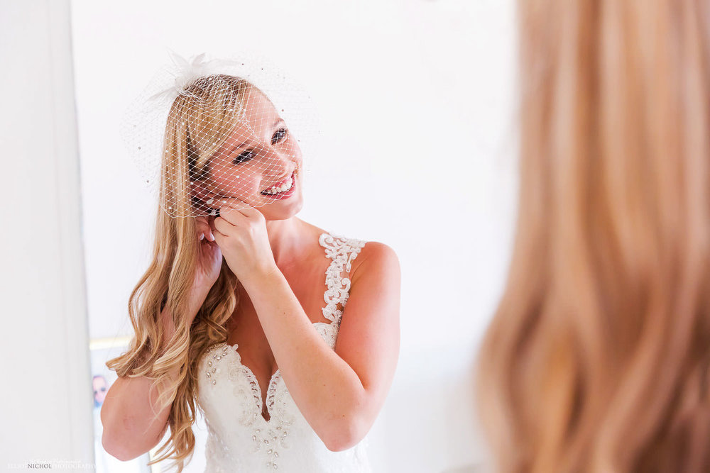 Bride putting her wedding earrings in at the Palace Hotel in Sliema, Malta while she gets ready for her wedding day.