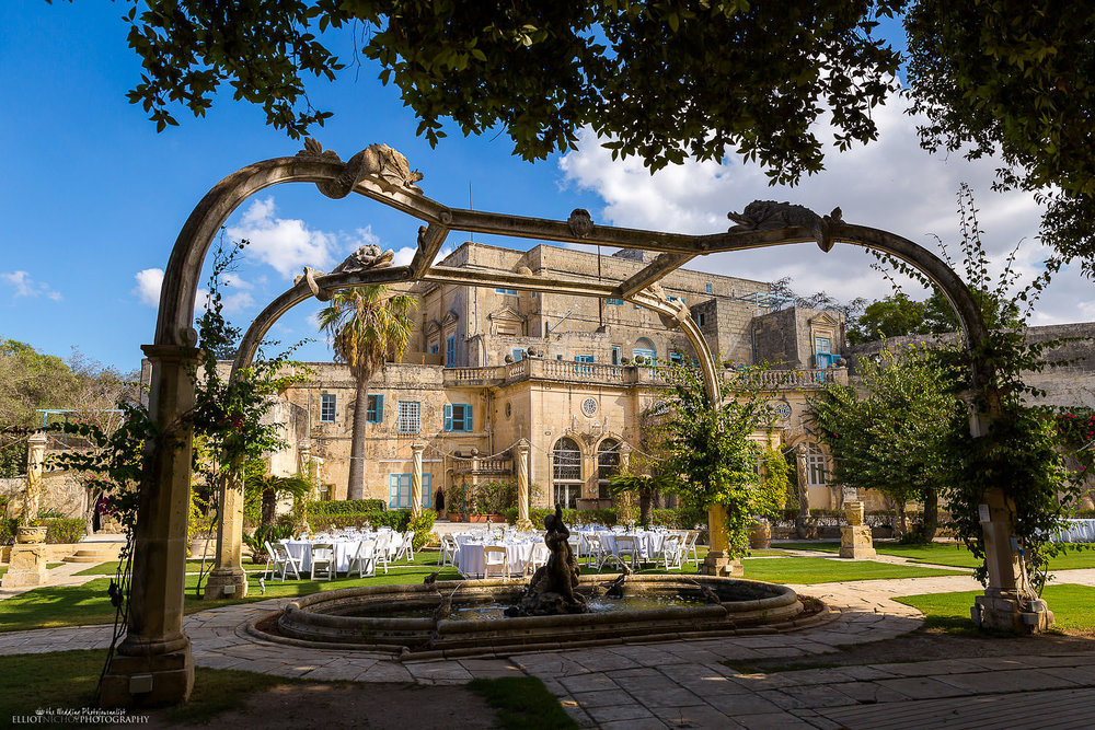View of the Dolphin fountain and wedding reception setup within the gardens of Villa Bologna, Malta.