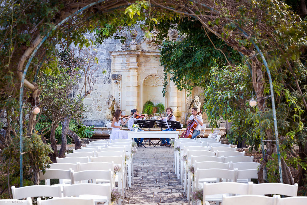 musicians playing before the wedding ceremony while guests arrive at the Villa Bologna in Malta.