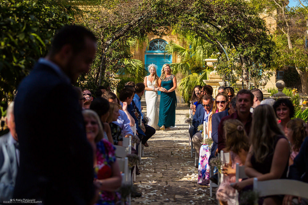 Bride arrives with her mother at the garden wedding ceremony within the Baroque garden at Villa Bologna, Malta.
