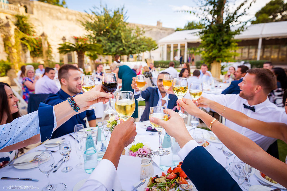 Wedding guests rise their glasses for a toast during the wedding reception in the gardens of the Villa Bologna, Malta.