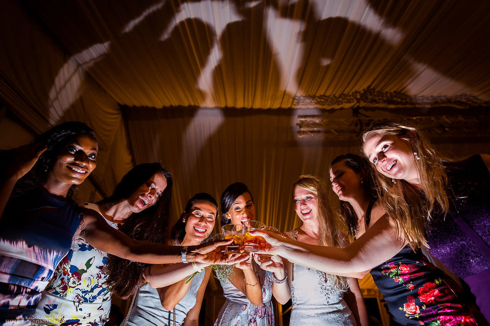 Female wedding guests and bride toasting each other at Villa Bologna. Wedding destination photographer Elliot Nichol.