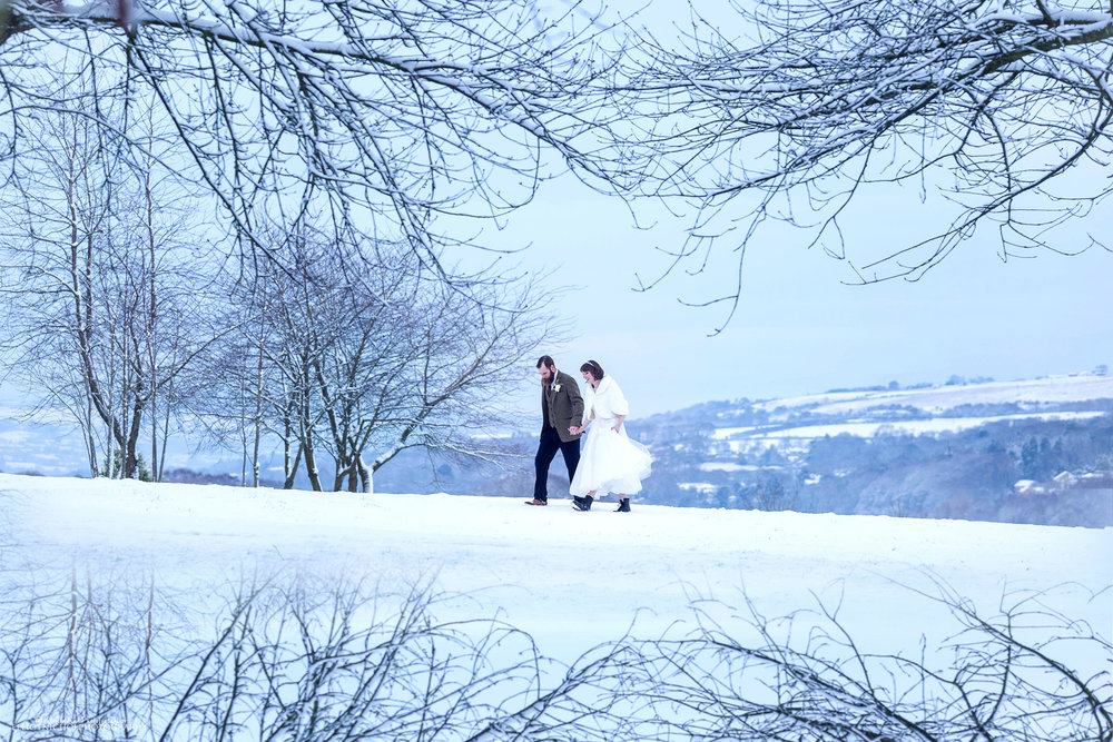Newlyweds walk through the countryside with a fresh blanket of snow on their romantic winter wedding.