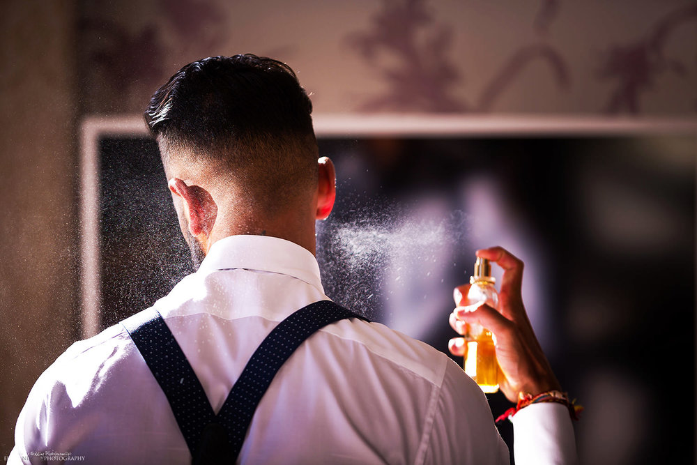 Wedding Groom applying aftershave before going to the wedding reception.