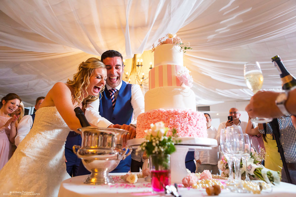 Northeast wedding photography. Bride and Groom having fun cutting their wedding cake.