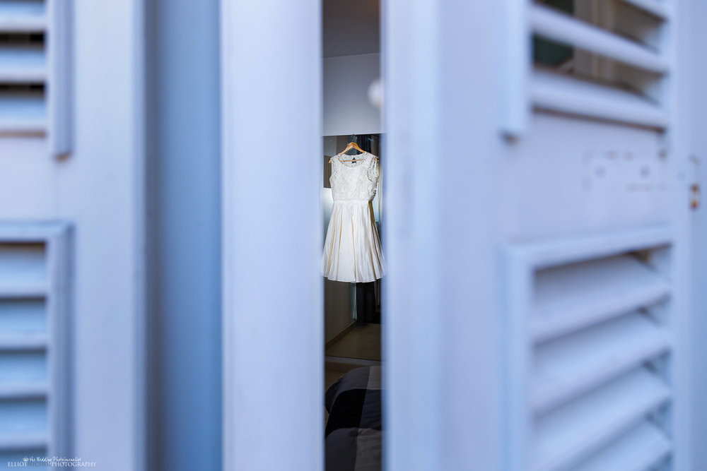 View of the Brides wedding dress through blue window shutters.