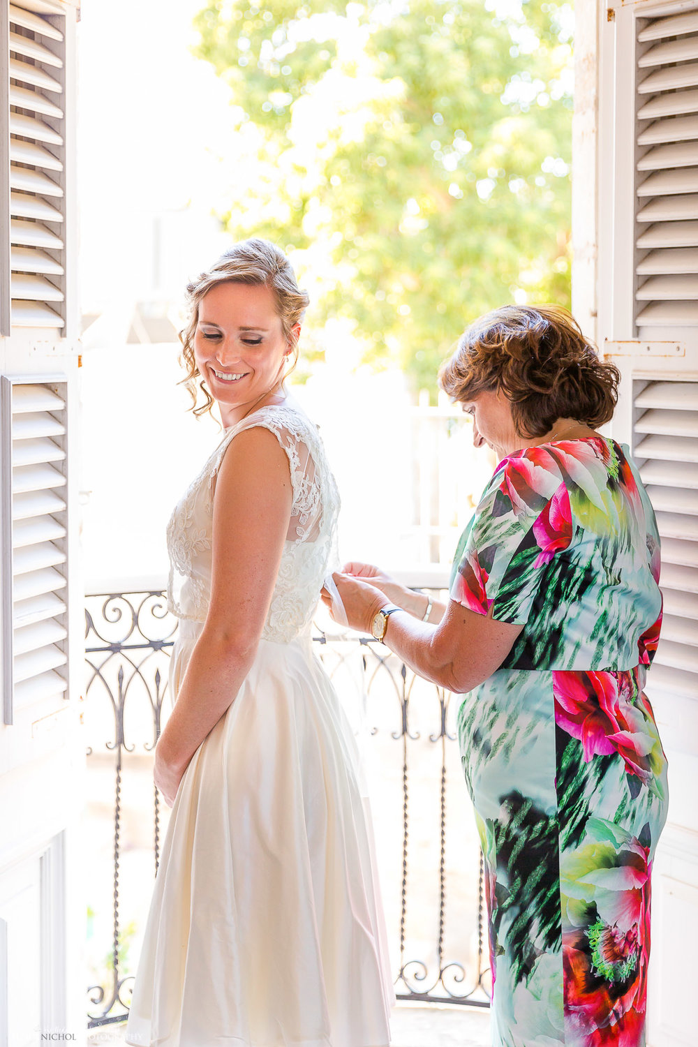 Bride being helped into her wedding dress by her mother. North East wedding Photography
