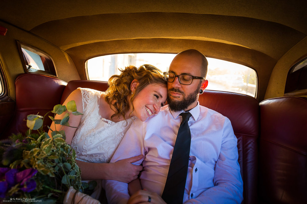 Bride and groom ride to their wedding reception venue in their vinatge wedding car. Elliot Nichol Photography.