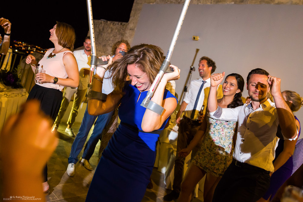 Wedding guest on crutches partying on the dance floor. Destination wedding photography.
