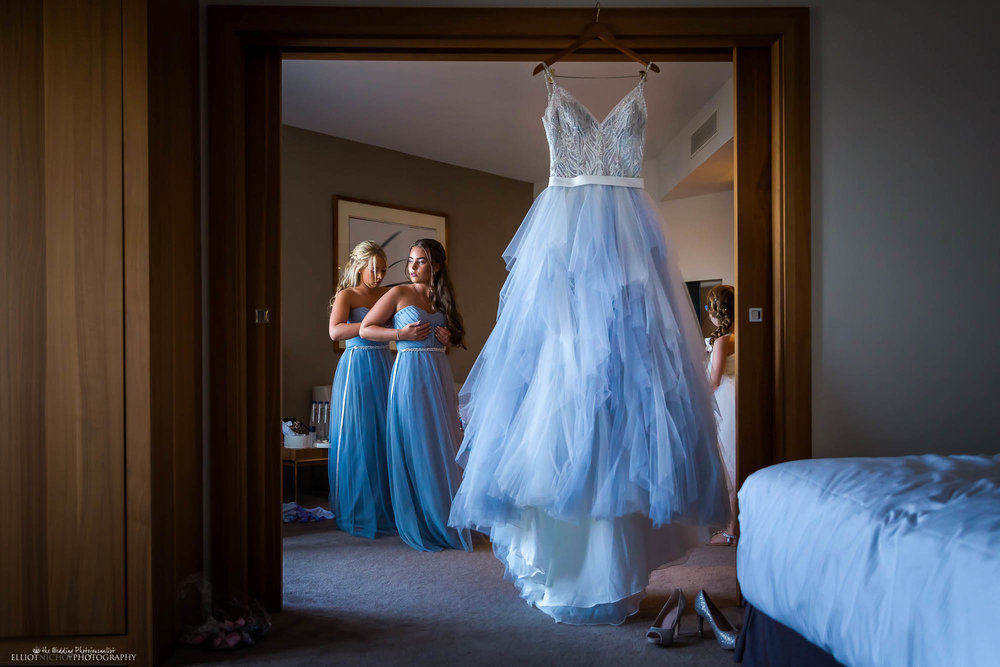 Bridesmaids getting ready next to brides blue wedding dress hanging in the room. Wedding photographer Elliot Nichol.