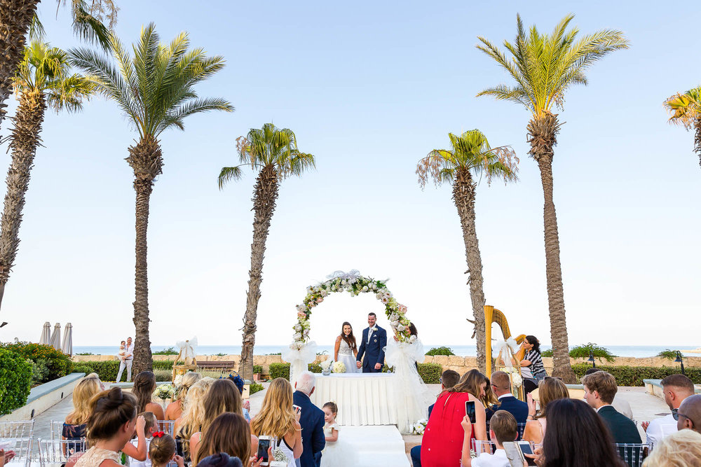 husband and wife stand in front of their wedding guests after marrying under the palm trees at their destination wedding ceremony.