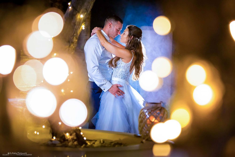 Portrait of bride and groom surrounded by fairylights. Blue wedding dress marriage