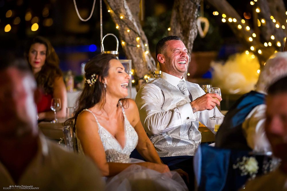 Newlyweds reaction to a funny wedding speech during their wedding reception.