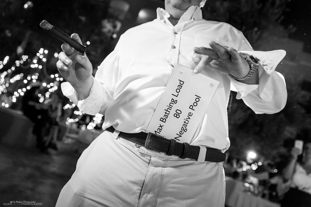 Wedding guest puts a swimming pool sign down the front of his trousers during partying at the wedding reception.