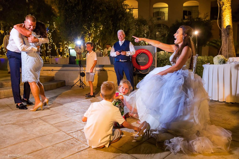 Bride laughs at grooms best man who is dancing with her mother.