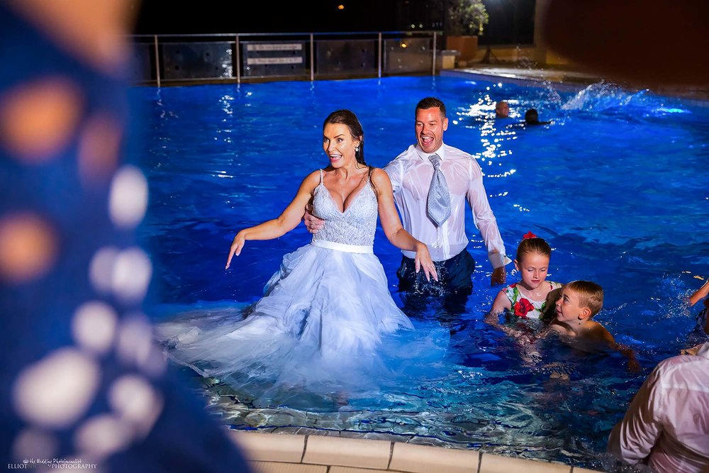 Bride in her blue wedding dress with her groom fully clothed in the pool. Trash the dress photo. Photography by Elliot Nichol.