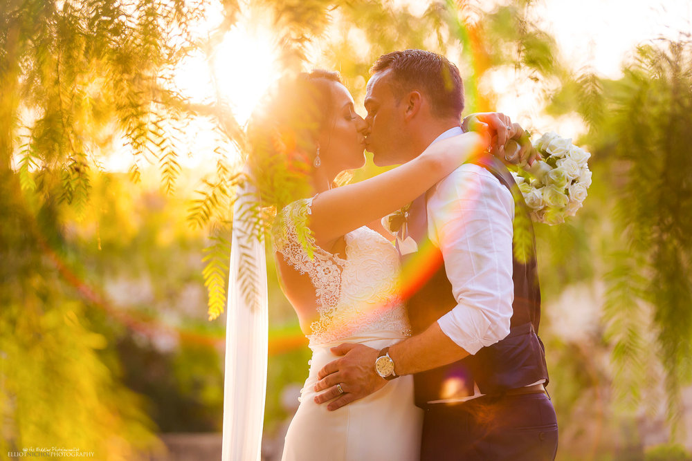 Bride and groom steal a kiss in the gardens of the their destination wedding venue. Photo by Elliot Nichol Photography, specialising in UK and EU destination weddings.