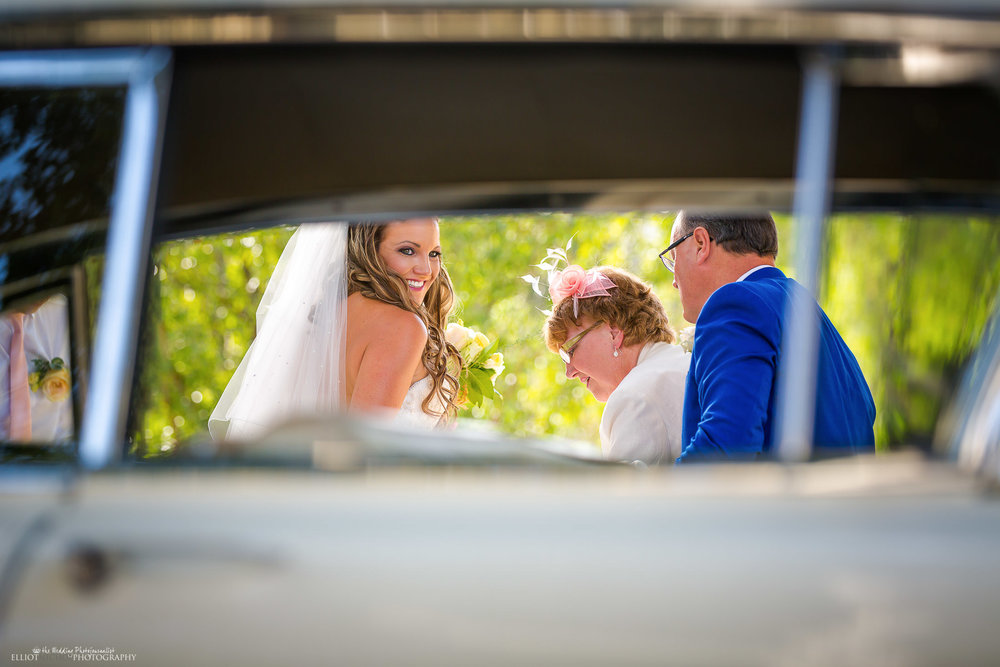 Bride leaves her vintage bridal car and heads off to the wedding ceremony with her parents. Photo by Elliot Nichol Photography.