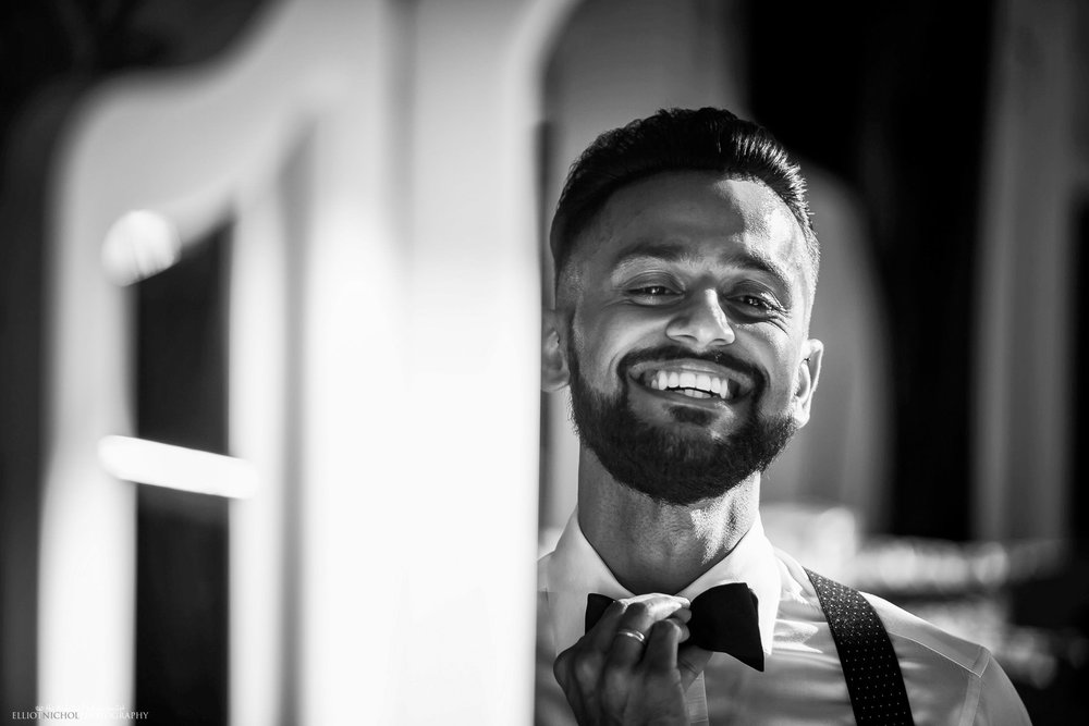 Happy groom fixes his bow tie in the mirror. Photo by Elliot Nichol Photography. UK & EU wedding photographer.