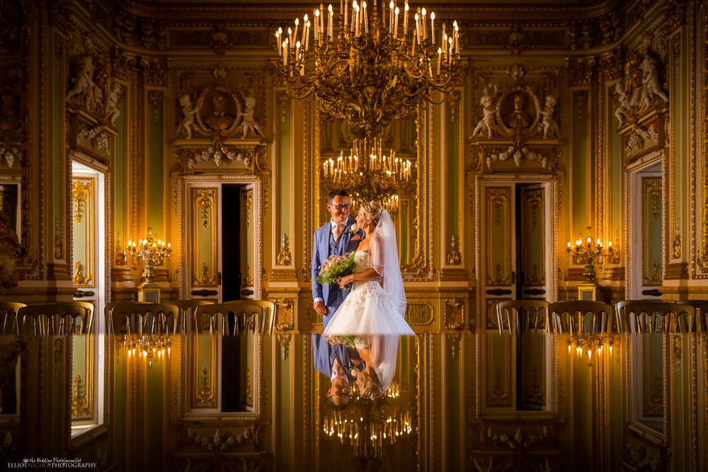 Bride and groom standing in the golden ballroom where their just had their wedding ceremony. Photo by Northeast wedding photographer Elliot Nichol.