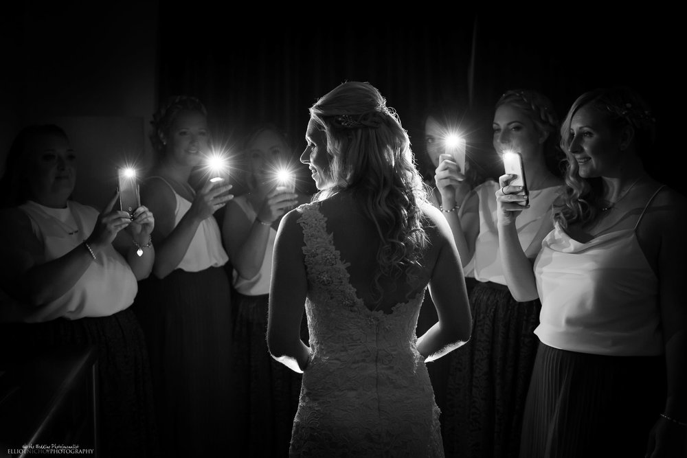 Bridesmaids light up the bride as they take photos of her. Photo by Elliot Nichol Photography. Northeast based photographer photographing weddings throughout the UK.