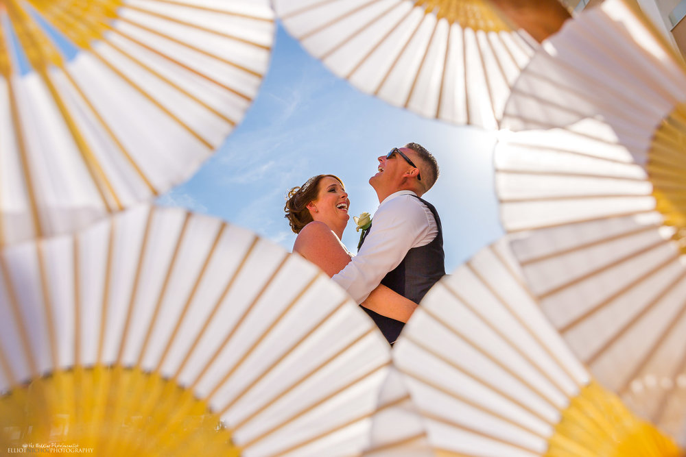 Fun Portrait of the bride and groom using fans. Photo by Elliot Nichol Photography. Creative wedding photography.