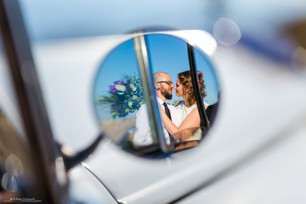 Reflection of the bride and groom about to kiss in their vintage Rolls Royce's side mirror. Photo by Wedding Photojournalist Elliot Nichol.
