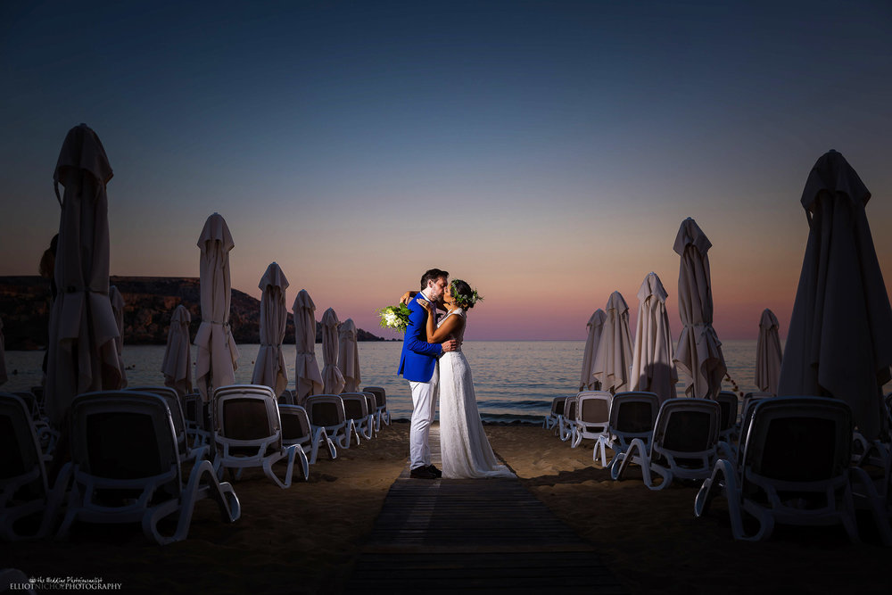 Destination wedding. Newlyweds on the beach at twilight. Photo by Elliot Nichol Photography.