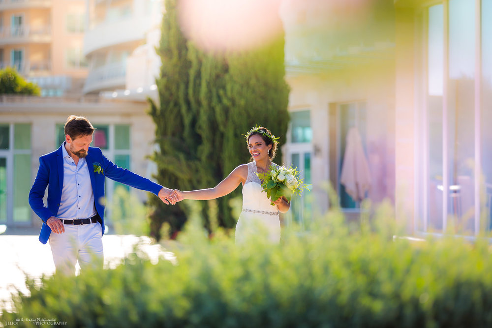 Newlyweds hand in hand enjoying their day. Photo by Elliot Nichol Photography.