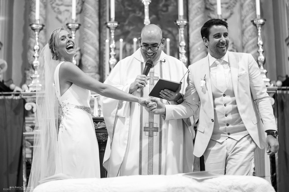 Bride and grooms funny reaction during the church wedding ceremony. Photo by Elliot Nichol Photography.