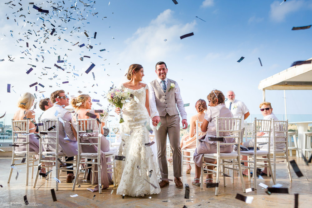 Bride and groom walk down the aisle under a shower of silver confetti. Photo by Elliot Nichol Photography based in Newcastle Upon Tyne.
