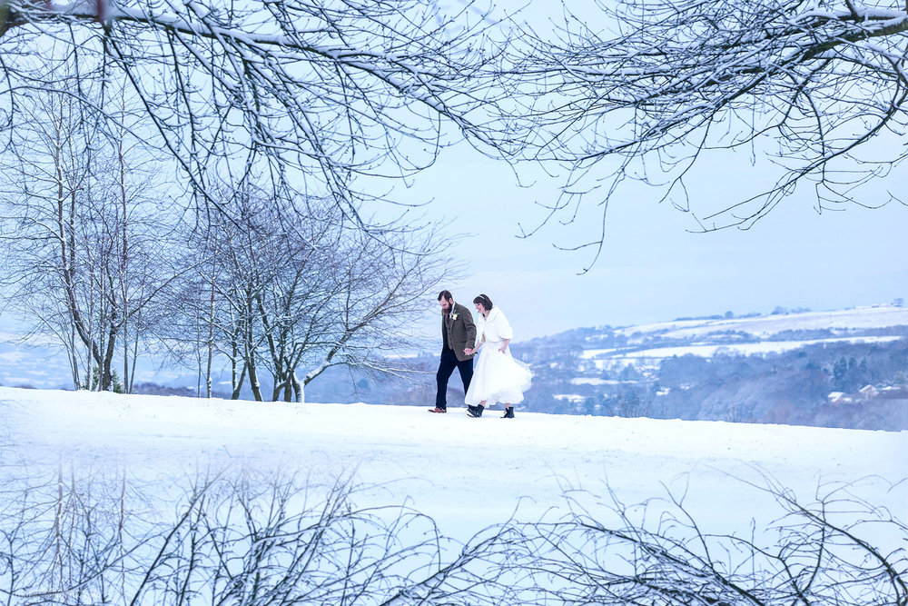 White winter wedding in Northumberland in the North East of England. Bride and groom walking thorough the frozen english countryside. Photo by Newcastle photographer Elliot Nichol.
