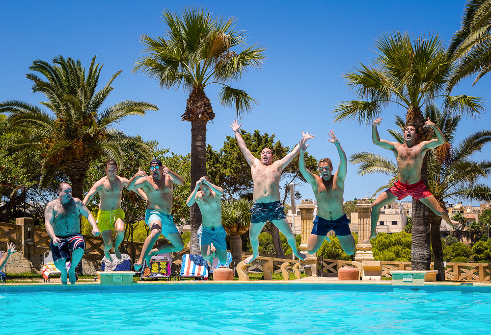 Groom and his groomsmen jumping into their villa's pool before the wedding. Photo by Elliot Nichol Photography.
