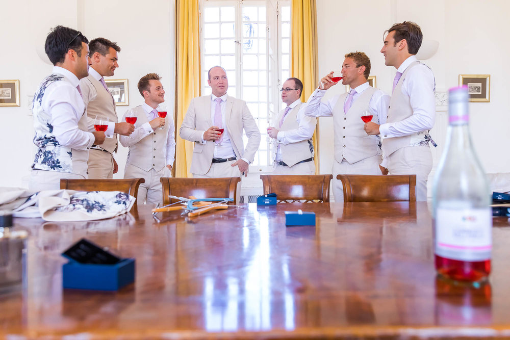 Groom having a drink with his groomsmen at his destination wedding villa. Photo by Elliot Nichol Photography.