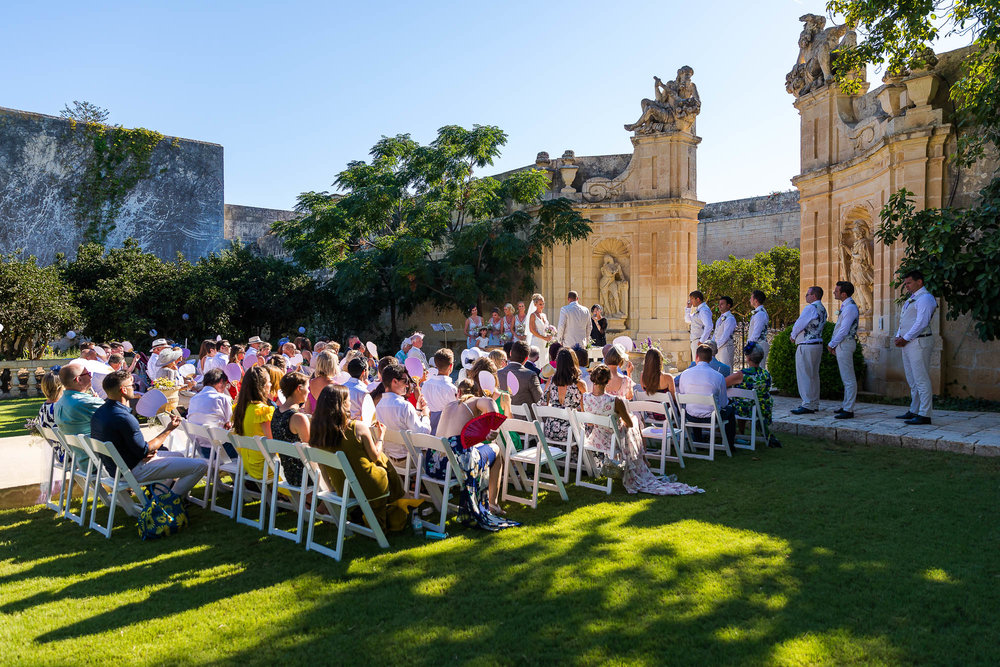 Overview of the garden wedding ceremony at Villa Bologna in Malta. Destination wedding photography by Elliot Nichol.