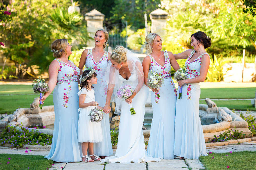 Bride, bridesmaids and flower girl in a informal portrait. Photo by Elliot Nichol Photography.