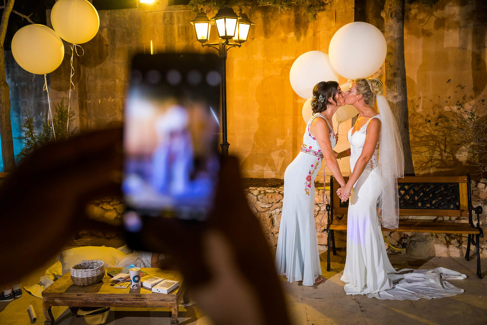 Bride kisses her bridesmaid while a wedding guest takes a photo of it on their mobile phone. Photo by Elliot Nichol Photography.