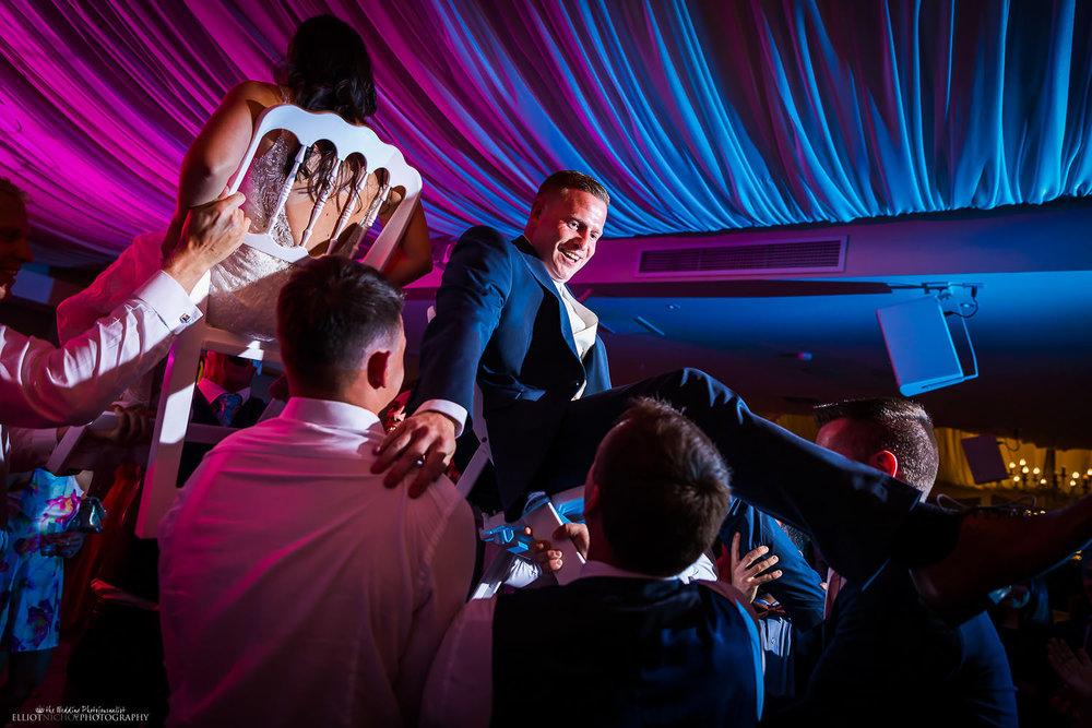 Bride and groom get lifted while sitting on chairs into the air during their wedding reception party. Photo by Northeast wedding photographer Elliot Nichol.