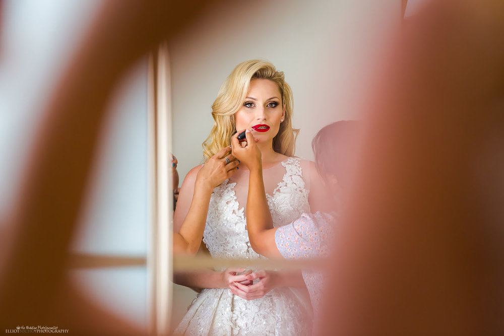 Bride getting her makeup applied by her makeup artists. Photo by Elliot Nichol Photography.