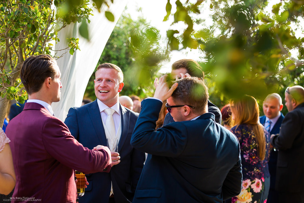 Groom enjoying mingling with his wedding guests. Photo by Elliot Nichol Photography.