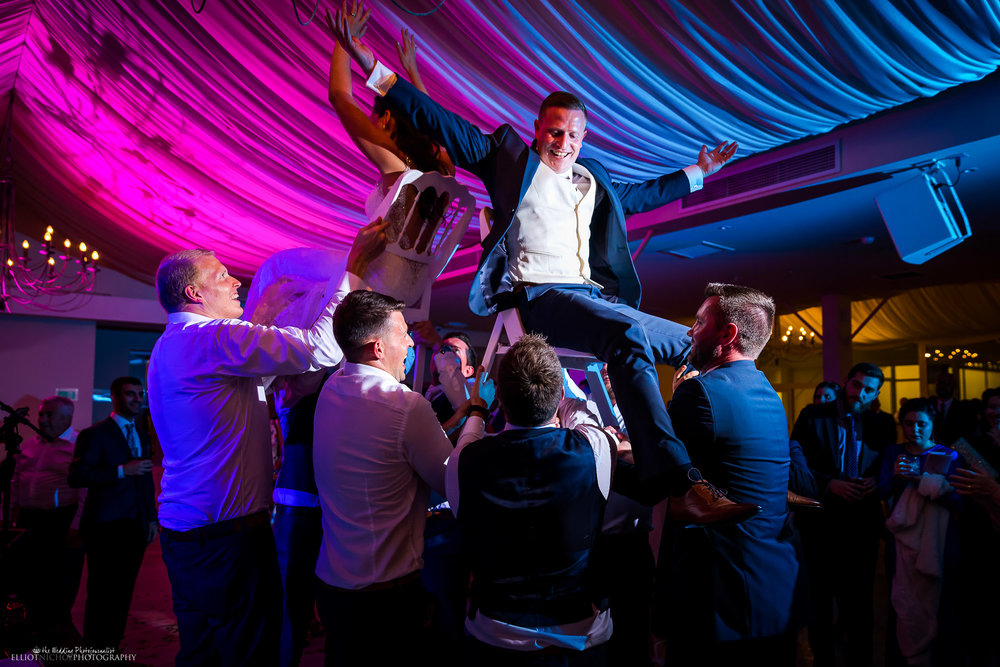 Bride and groom are lifted into the air during their destination wedding reception. Photo by Elliot Nichol Photography.