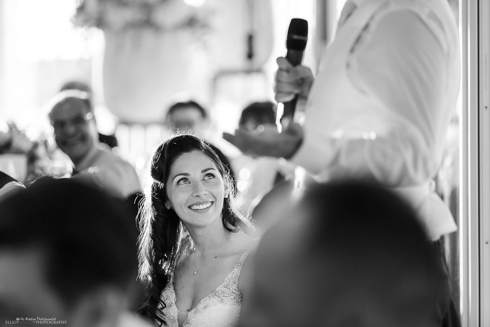 Bride enjoys her groom's wedding reception speech. Photo by wedding photojournalist Elliot Nichol.