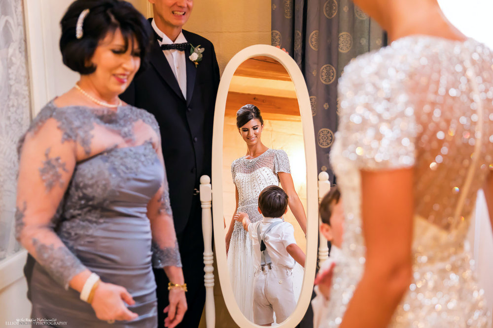 Bride's family surrounds her while she looks at her mirror refection in her wedding dress. Photo by Northeast wedding photographer Elliot Nichol.